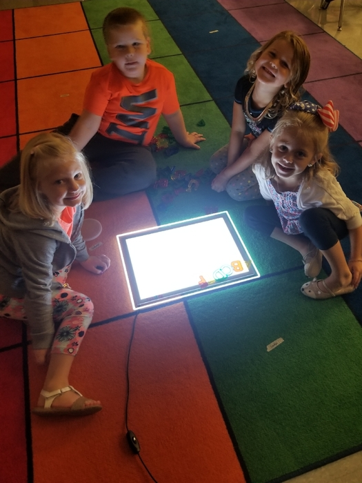 Mrs. Laue's friends are working hard on ABC order at the light table.
